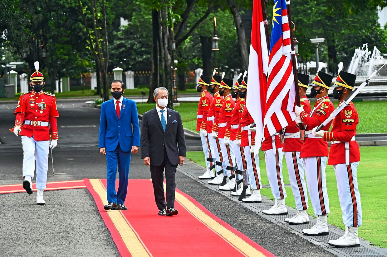 Meeting of leaders: Jokowi and Muhyiddin (right) inspecting a guard of honour at the presidential palace in Jakarta. — AFP
