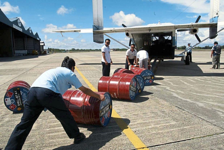 Layang Layang Aerospace Skyvan staffs rolling the barrels of aircraft fuel to be flown to bario at Miri airport.
