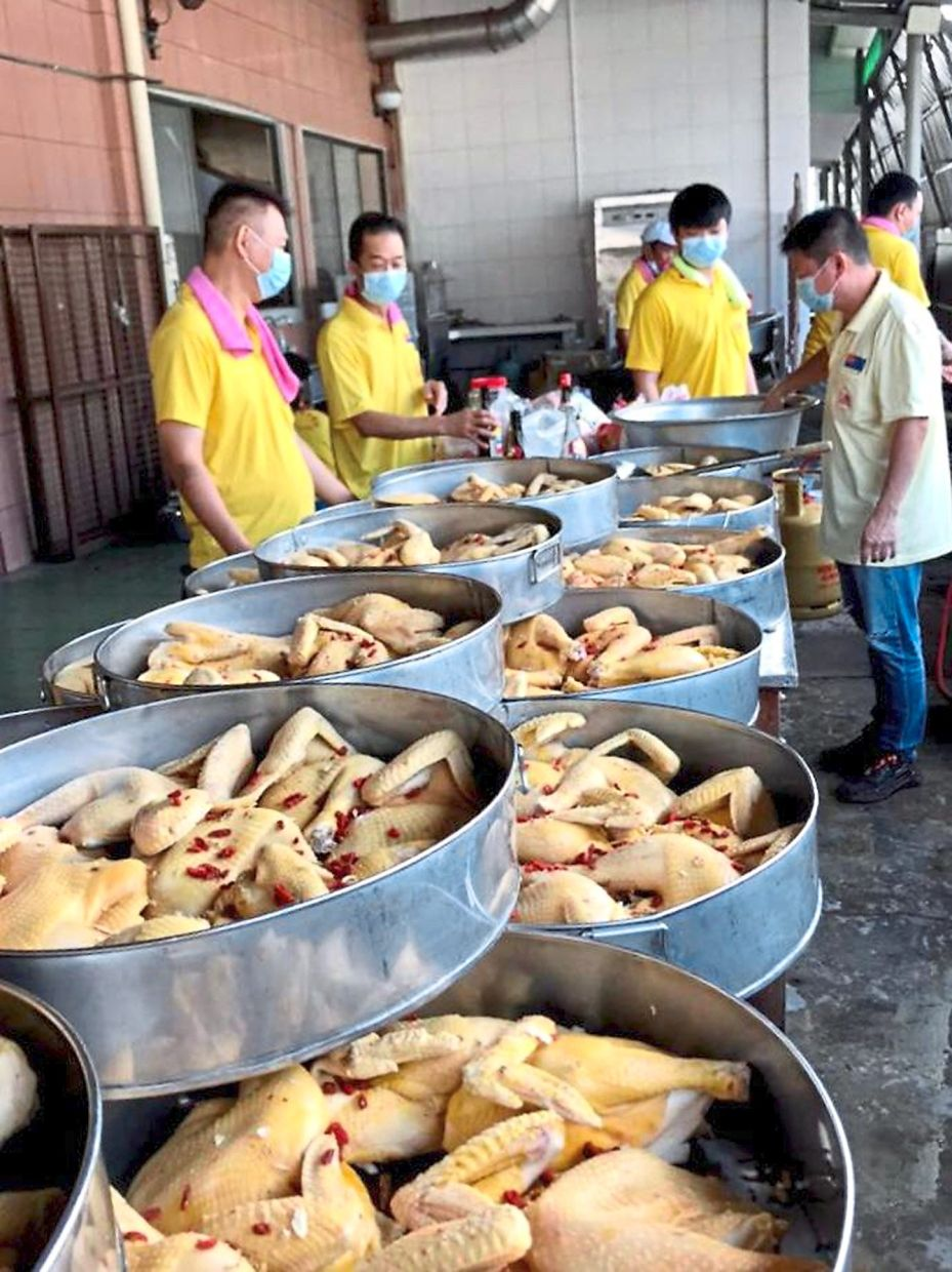 Chefs busy cooking a wholesome meal at the Kluang Che Luan Khor Moral Uplifting Society premises. The meals will be packed and frozen for the less fortunate to enjoy on Chinese New Year eve.
