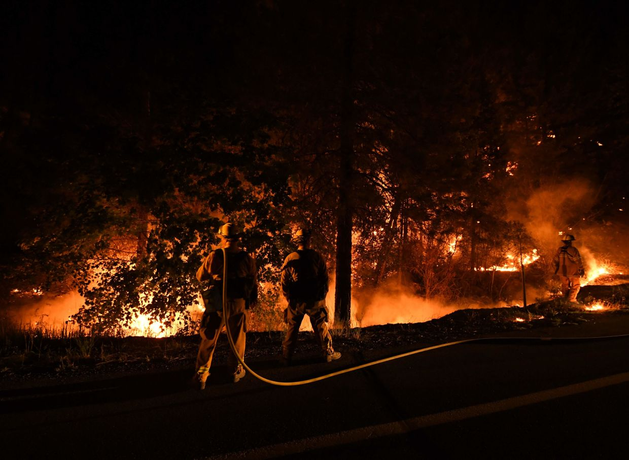 Firefighters try to contain flames from the Carr fire as it spreads towards the town of Douglas City near Redding, California, on July 30, 2018. — AFP
