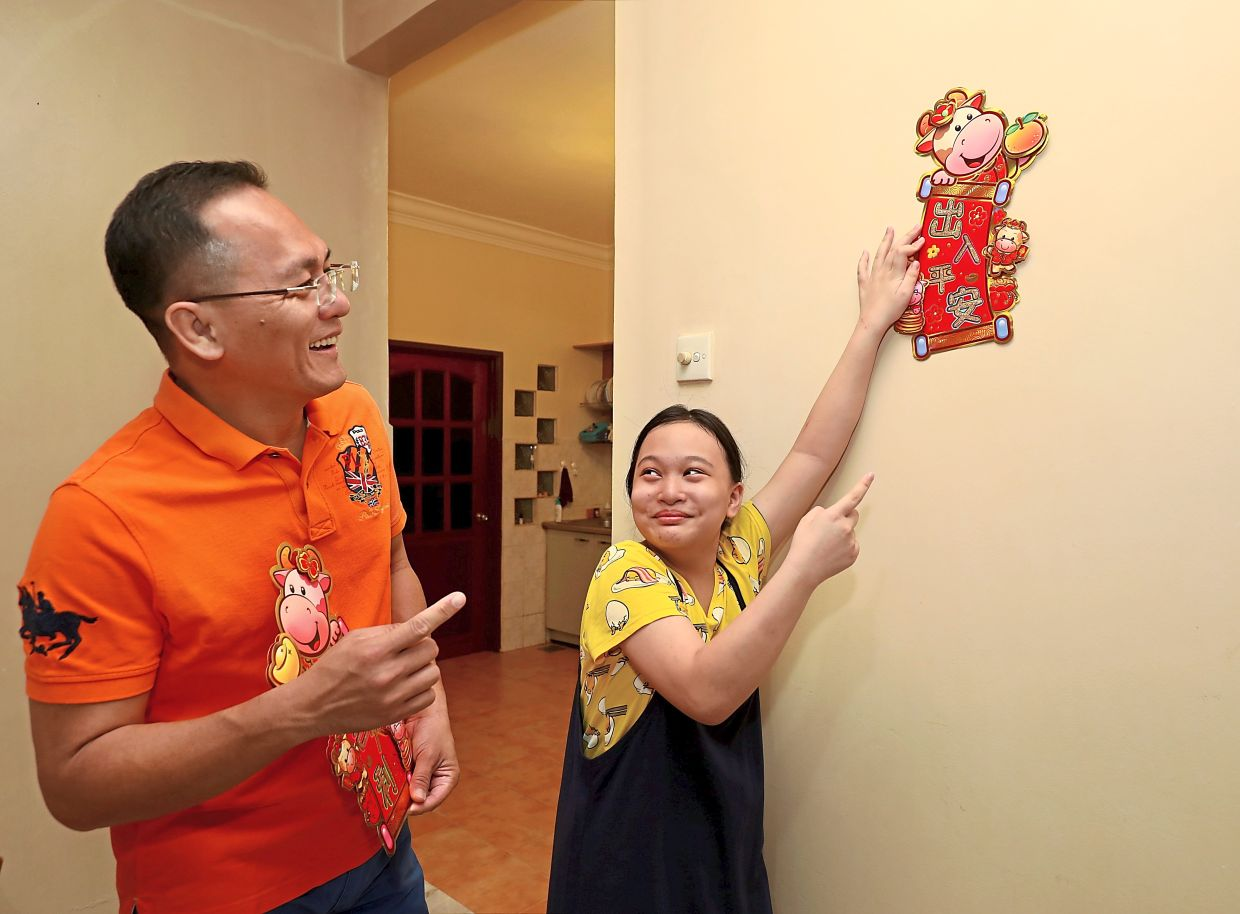 Z Qin helping her father BG put up CNY decorations at their home.