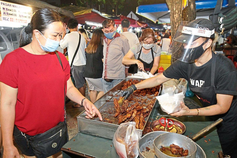 A belacan chicken seller wearing a face shield at the Macallum Street Ghaut night market. — Filepic
