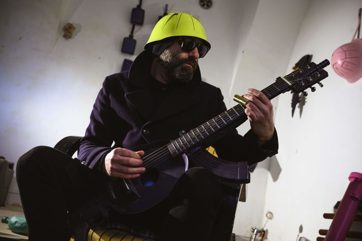 Srdjan Sarovic, visual artist and a war veteran, plays on a guitar made out of M70 rifle and a helmet, made by Serbian sculptor Nikola Macura at his studio, in Novi Sad. Photo: AFP
