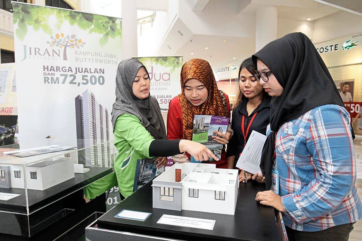 PDC sales and marketing assistant Noramasni Azmi (left) briefing visitors about the Jiran Residensi project at StarProperty.my Fair 2018 at Gurney Paragon Mall, Penang. — Filepic