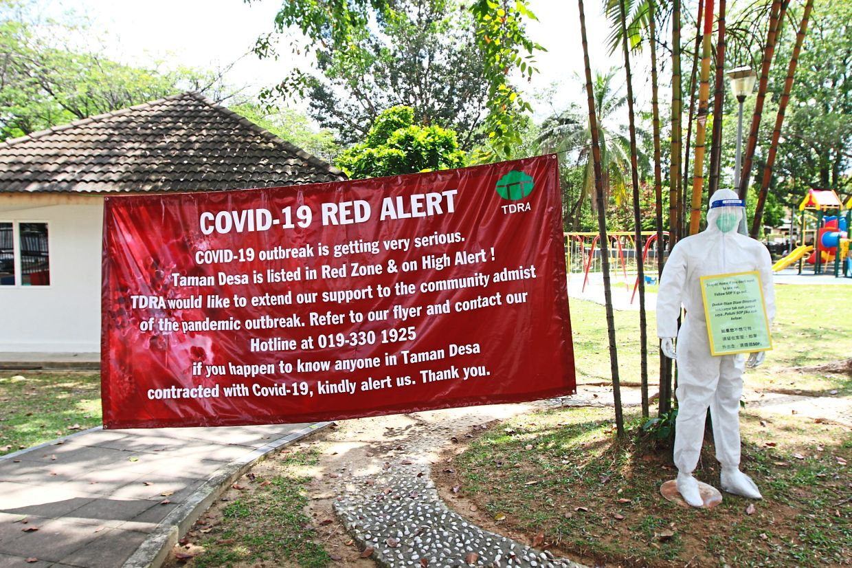 The banner put up by Taman Desa Residents Association informing people of the hotline they can call for help.