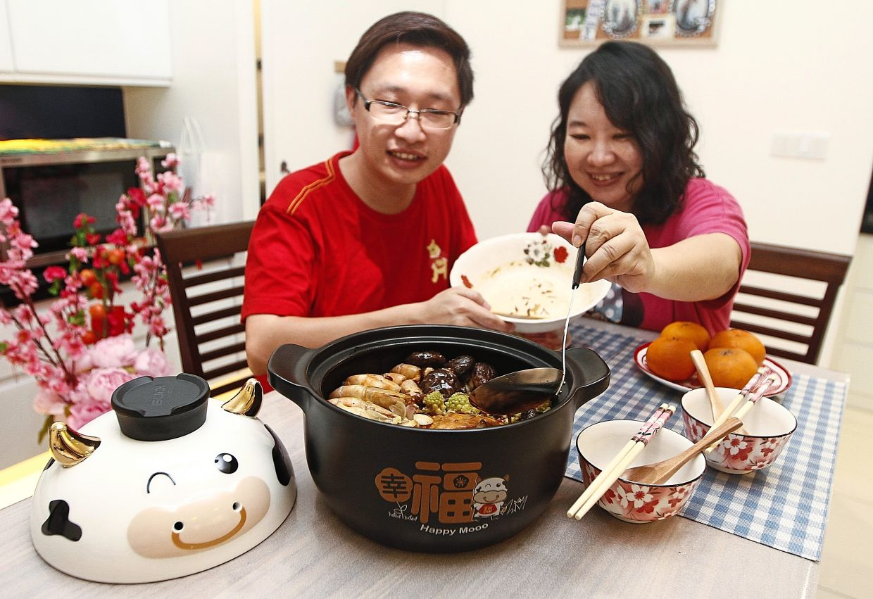 Tan (left) and Ng enjoying their fusion version of Poon Choy at their home in Sungai Ara.