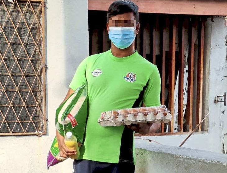 A foreign worker under home quarantine holding food supplies provided by TDRA.