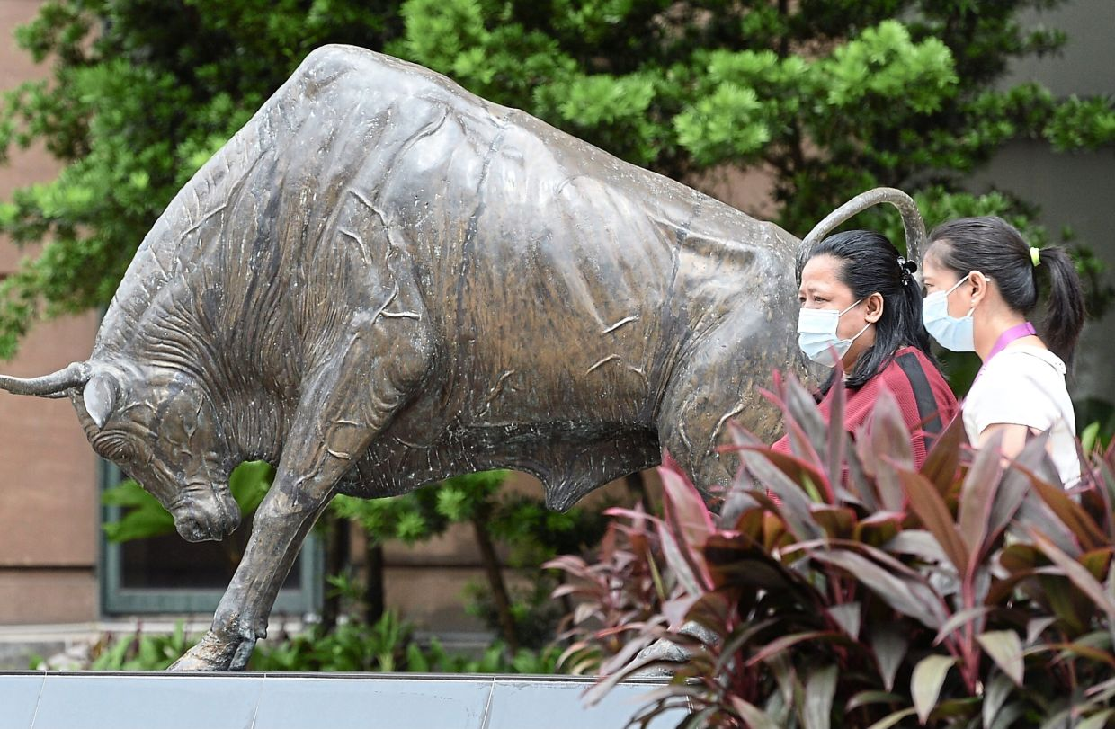 On the rise: People walk past the bull statue at the Bursa building in Kuala Lumpur. The FBM KLCI, which has been on a decline since mid-December 2020, has notched over 40 points since the start of February and has once again returned to above the 1,600-point mark.