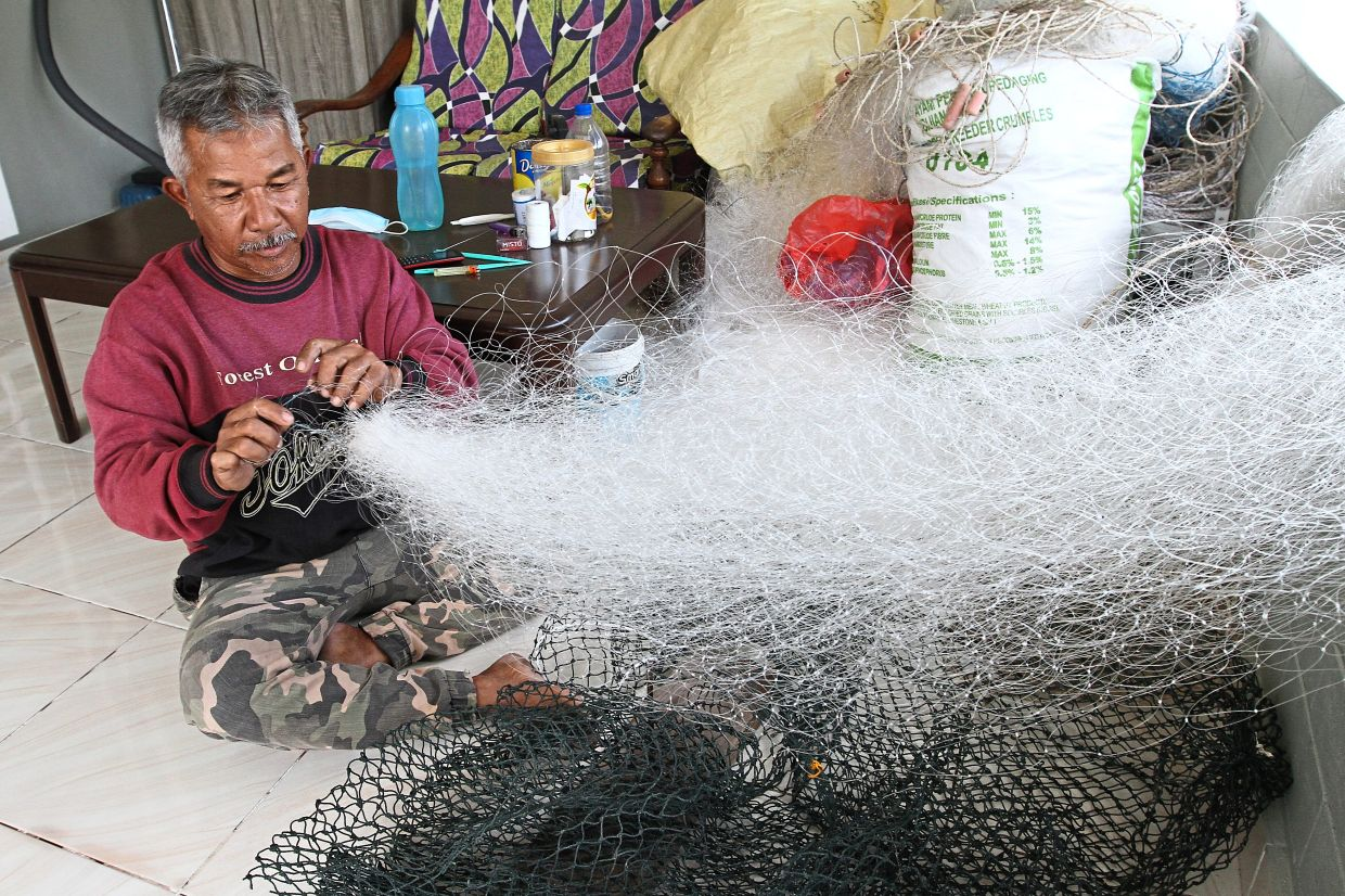 Abd Aziz has to constantly repair or replace his fishing nets because they get damaged by ships' anchors.