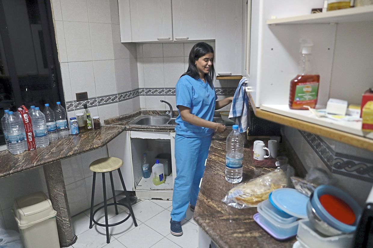 Ghosh cleaning dishes at a temporary apartment provided by Baytna Baytak.