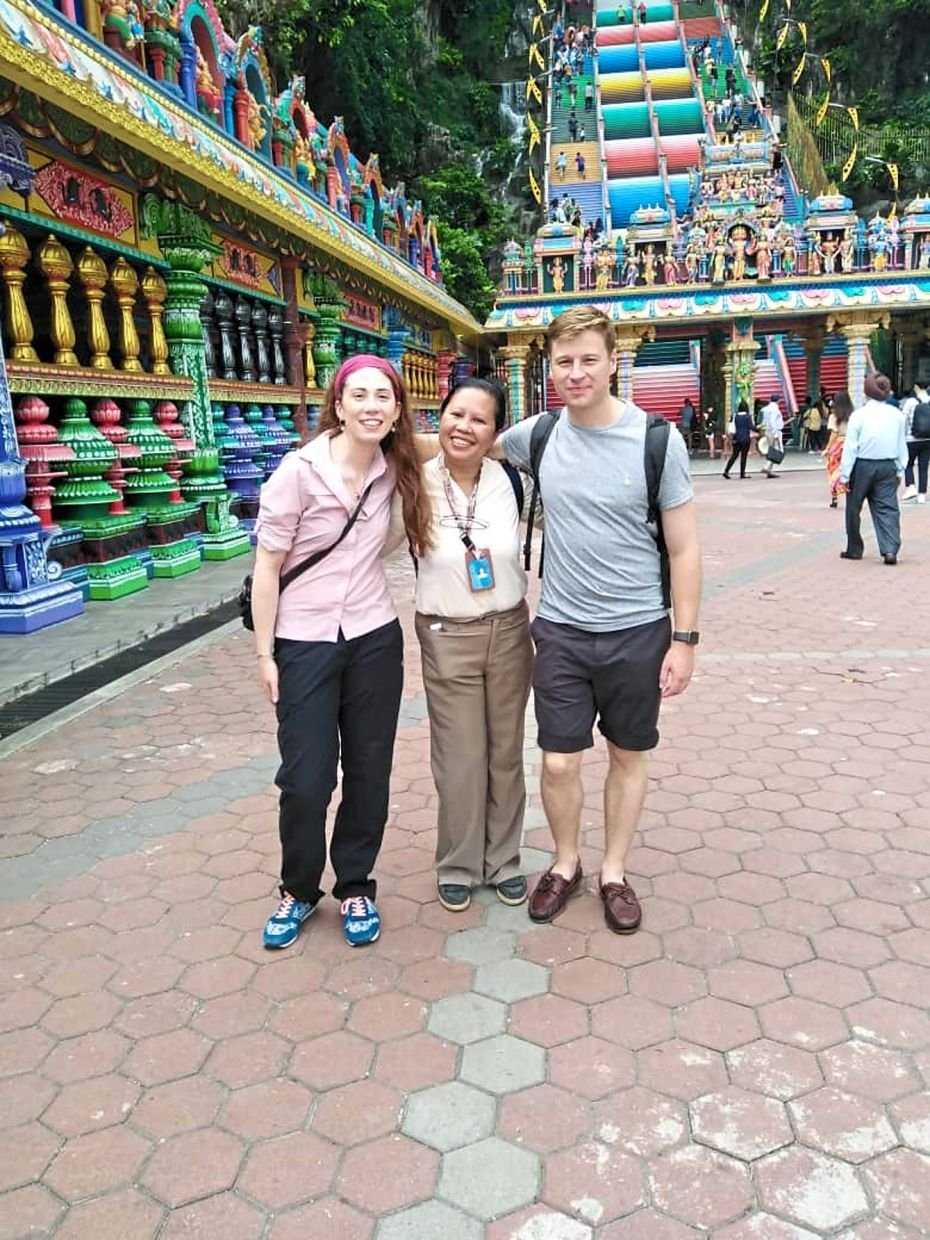 Catherine flanked by foreign tourists she brought to Batu Caves, Selangor in November 2019.
