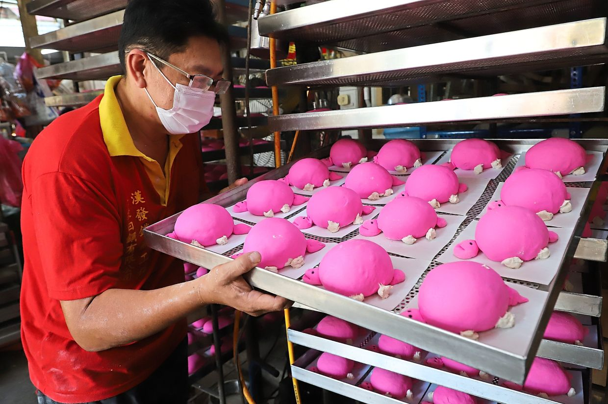 Trays of mee koo are being placed in a multi-tiered rack to be steamed.
