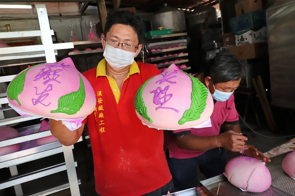 Beng Keat showing the peach-shaped longevity buns with auspicious words while his father Lye Soon prepares another one.
