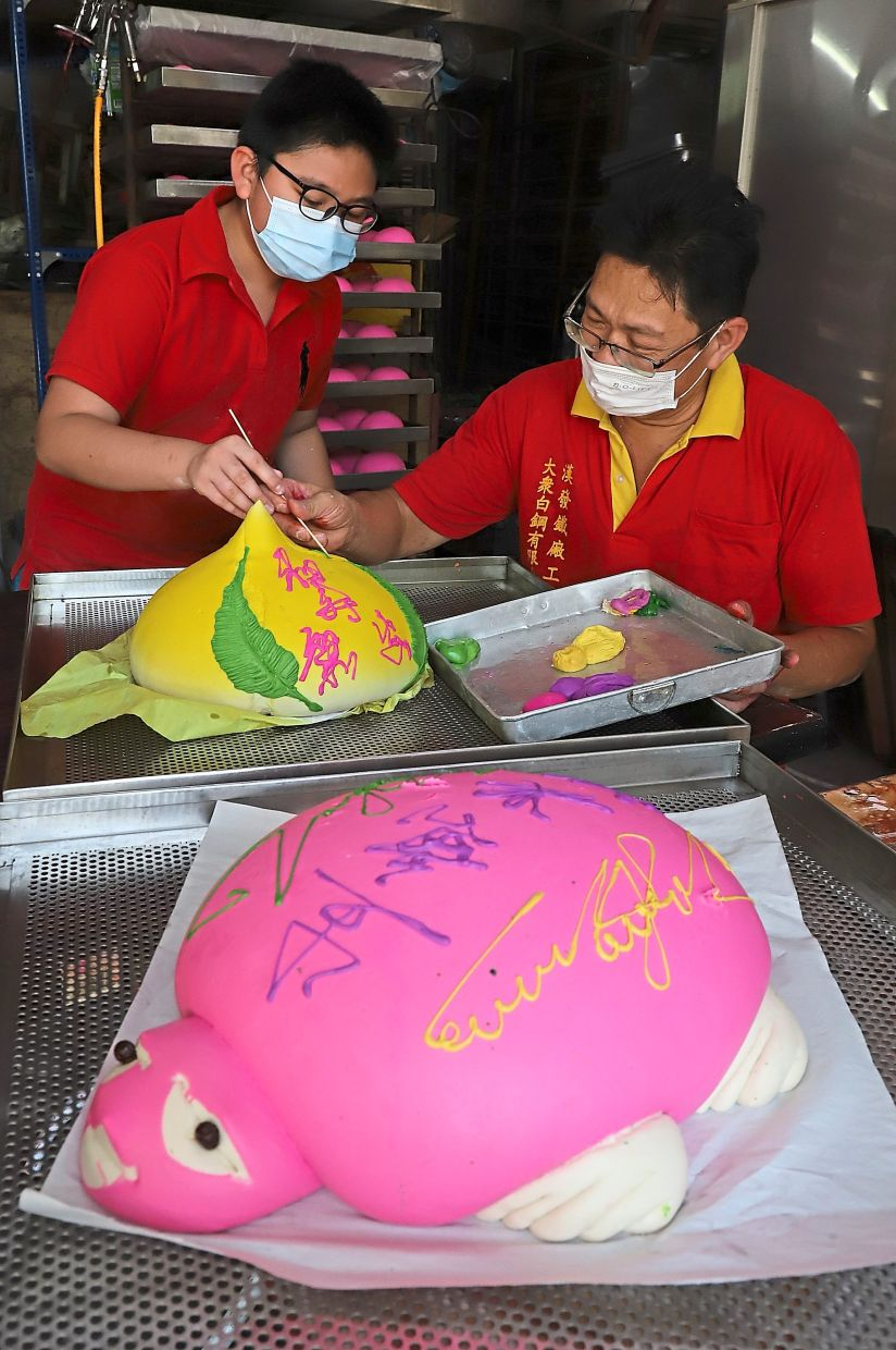 Beng Keat (right) showing Vernon how to paint auspicious Chinese characters on the peach-shaped bun in conjunction with Jade Emperor God's birthday celebration at their house in Jelutong, Penang. — Photos: LIM BENG TATT/The Star