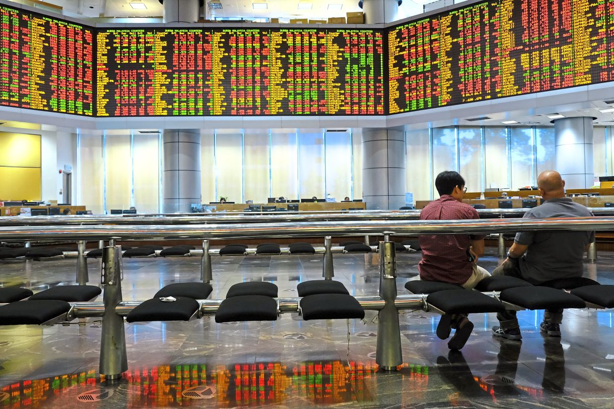 People sit at a trading gallery of an investment bank in Kuala Lumpur. For 2021, analysts estimate a sharp net profit recovery for the stock market by some 59% – the highest in the Asia-Pacific. — Bloomberg