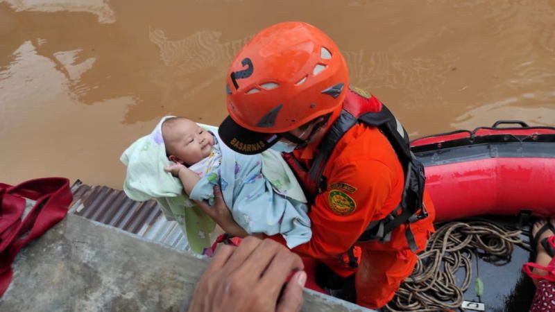 Indonesian Search and Rescue Agency (Basarnas) personnel evacuates a baby in an area affected by floods in Jakarta, Indonesia, February 20, 2021. Courtesy of Indonesia's Search and Rescue Agency (Basarnas) - Reuters