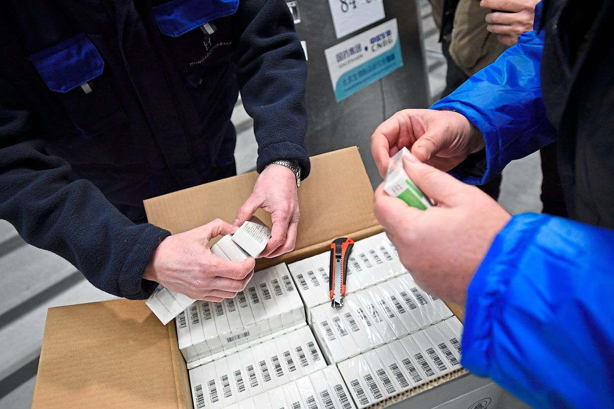 Workers inspect a box containing Covid-19 vaccines developed by Sinopharm upon delivery at a pharmaceutical wholesaler in Budapest, Hungary, recently. — AP