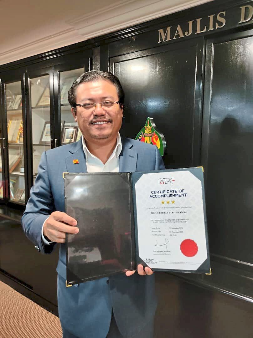 Mohd Azhar holding the Quality Environmental Management System (QE/5S) certification by Malaysian Productivity Corporation.