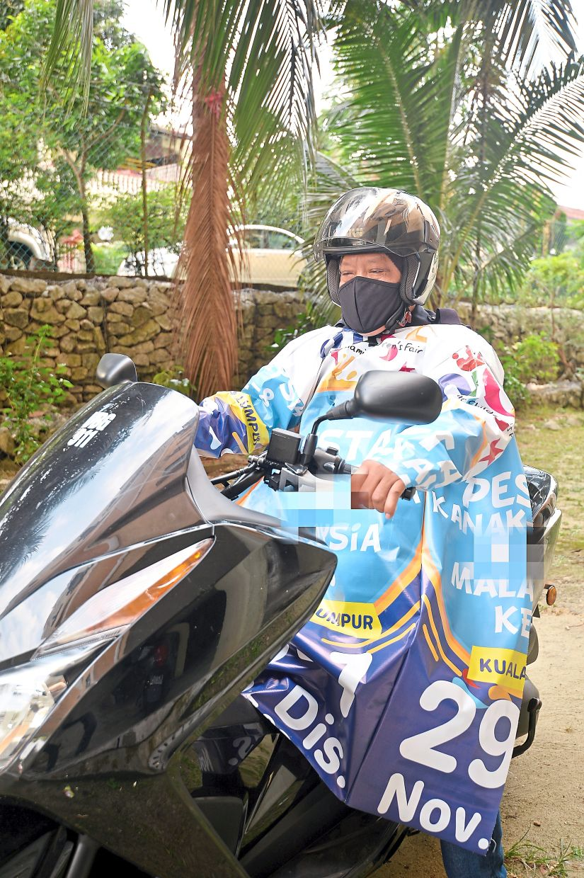 A PPR Pekan Kepong resident wearing a raincoat made from an old banner.