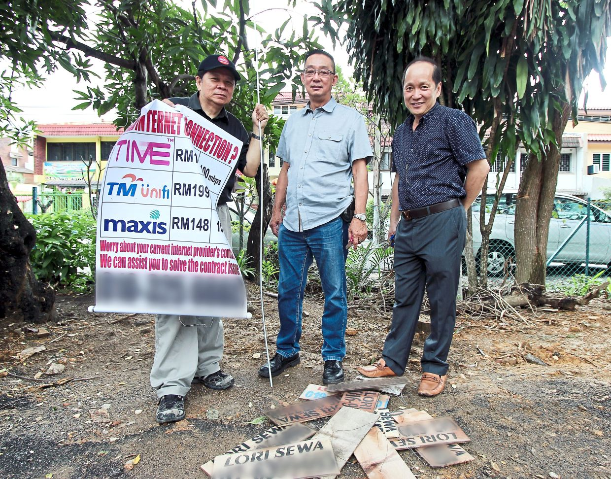 Taman Desa Residents Association (TDRA) committee member Francis Tan, Wong and TDRA adviser William Chan showing some of the illegal advertisements they removed around Taman Desa. This filepic was taken before the Covid-19 pandemic.