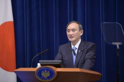 Japan's Suga sorry for his son's wining, dining with bureaucrats