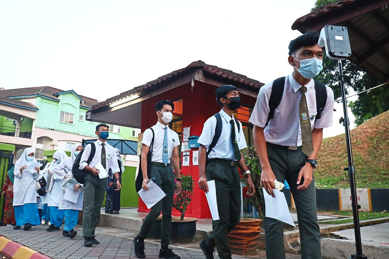 Ready for the test: Candidates queuing up to take their temperature on the first day of the SPM examinations at SMK Bandar Tasik Puteri in Rawang. — FAIHAN GHANI/The Star