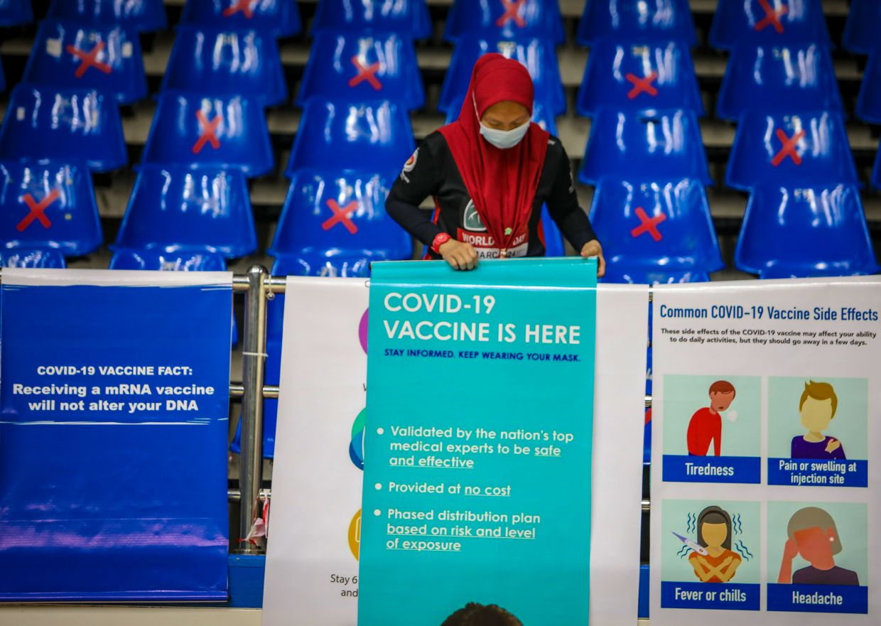 Nurse Nur Khairunnissa Mohamad Salleh adjusting a vaccination banner at the Indoor Stadium in Kuching, where Sarawak's Covid-19 immunisation programme will be launched on Saturday (Feb 27).  — ZULAZHAR SHEBLEE/The Star