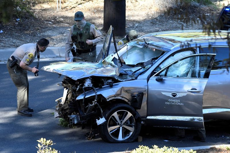 Los Angeles County Sheriffs Deputies inspect the vehicle of golfer Tiger Woods who was rushed to hospital after suffering multiple injuries after it was involved in a single-vehicle accident in Los Angeles California U.S. February 23 2021.  REUTERSGene Blevins