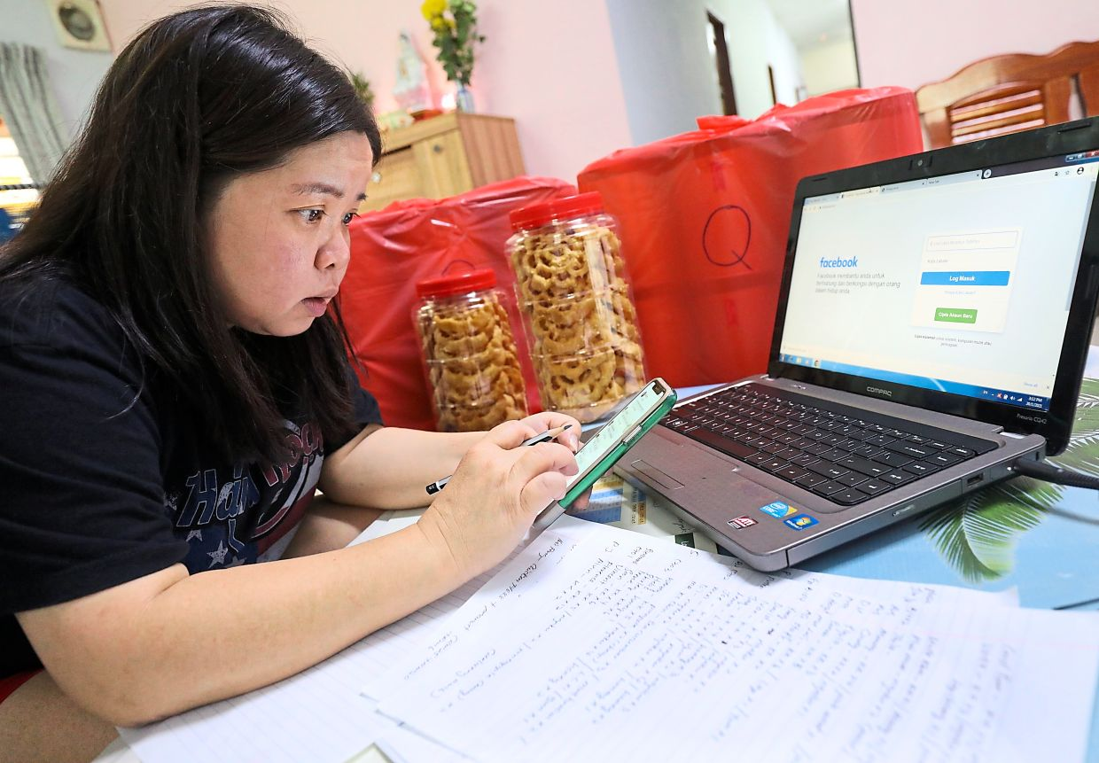 While waiting for the travel and tourism industry to pick up, travel agent Ng has learned to use social media to improve her food delivery business. Photo: The Star/Samuel Ong