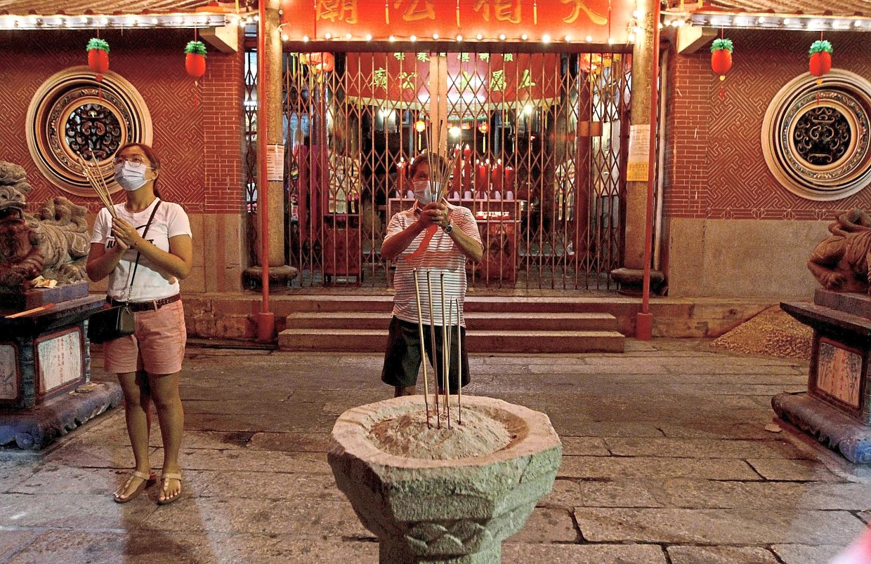 Eng and his daughter praying outside the closed temple.