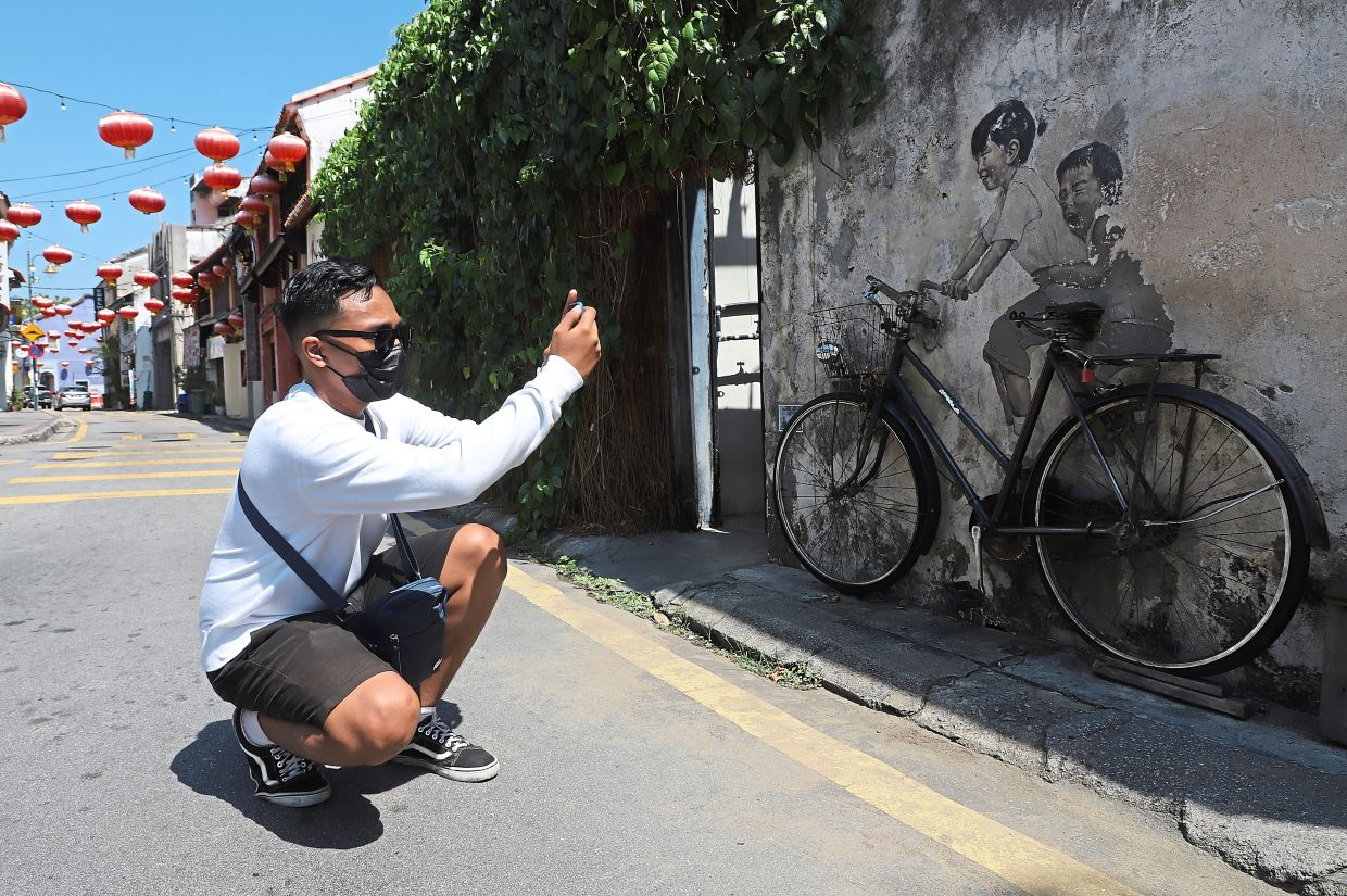 Amirul taking a picture of the 'Little Children on a Bicycle' mural along Armenian Street. —Photos: LIM BENG TATT/The Star