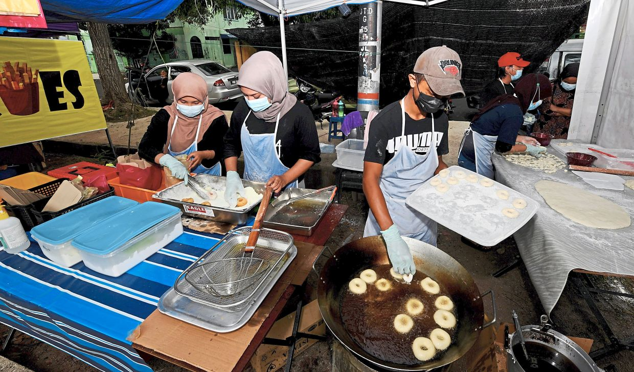 Nur Farahanah (second left) and workers preparing the milk doughnuts at the stall. — Bernama