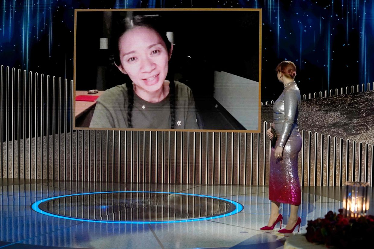 Chloe Zhao (on screen) accepting the Best Director - Motion Picture award for 'Nomadland' via video from Bryce Dallas Howard.