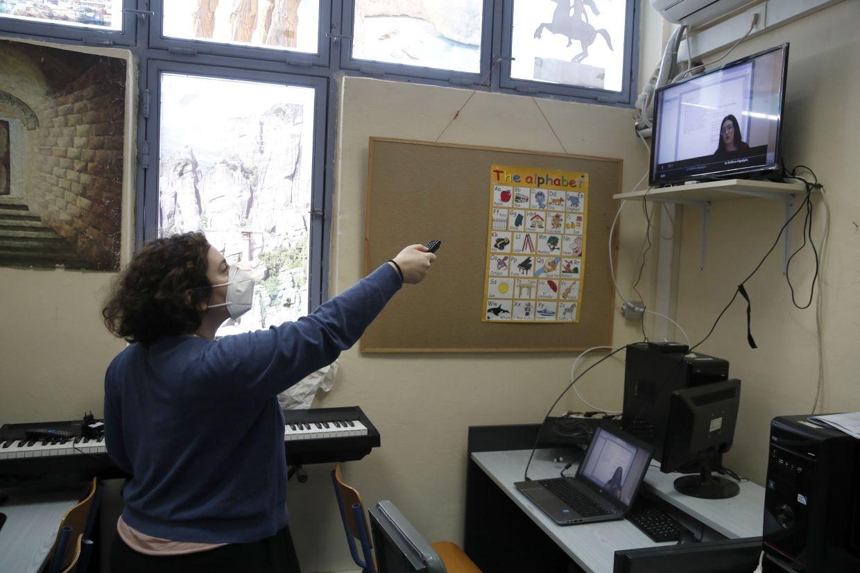 Computer teacher Evi Kontopoulou uses a remote control to find Prospathodas TV.