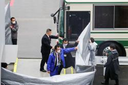 Men accused of aiding Ghosn escape arrive in Japan after extradition - TV