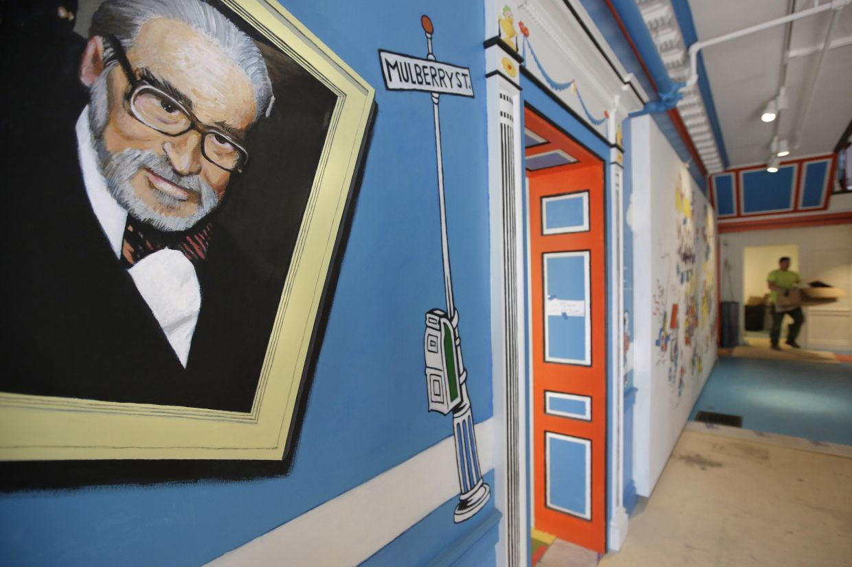 A painting that features Theodor Seuss Geisel, left, also known by his pen name Dr Seuss, covers part of a wall near an entrance at The Amazing World of Dr Seuss Museum, in Springfield, Massachusetts. Photo: AP