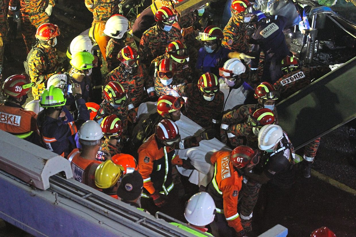 Grim task: Fire and Rescue Department personnel removing one of the victims from the rubble. — SHAARI CHEMAT/The Star