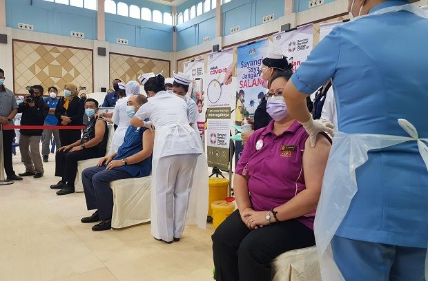 Datuk Seri Hajiji Noor (seated, middle), Datuk Dr Christina Rundi (seated, right) and Datuk Hazani Ghazali (seated, left) when receiving their first doses of vaccine during the state level vaccination launch Thursday (Mar 4).