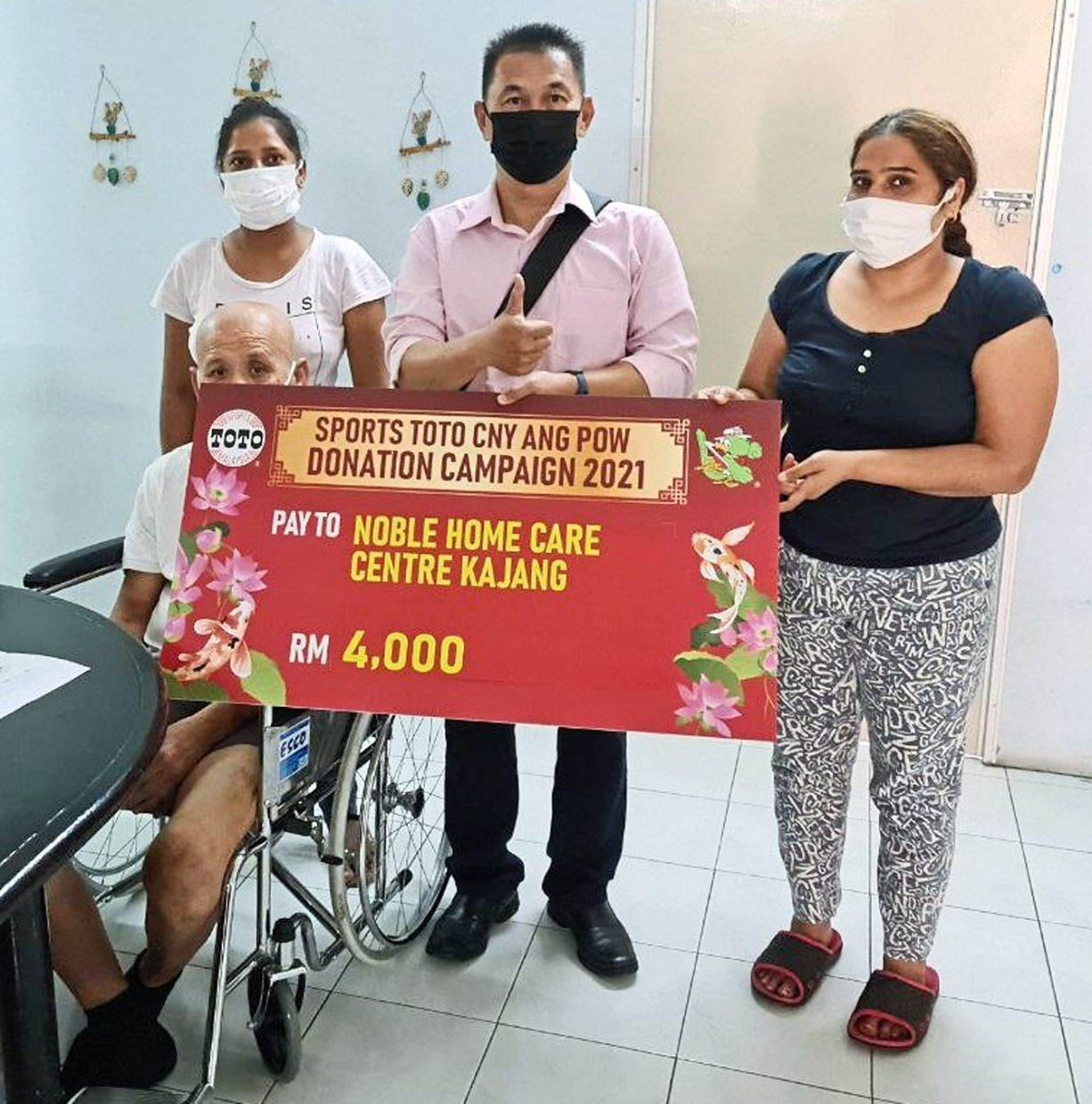 Noble Home Care Centre Kajang person-in-charge Tania Amanat (right) receiving a contribution from Sports Toto representative Mohd Rafiee Rashid (centre).