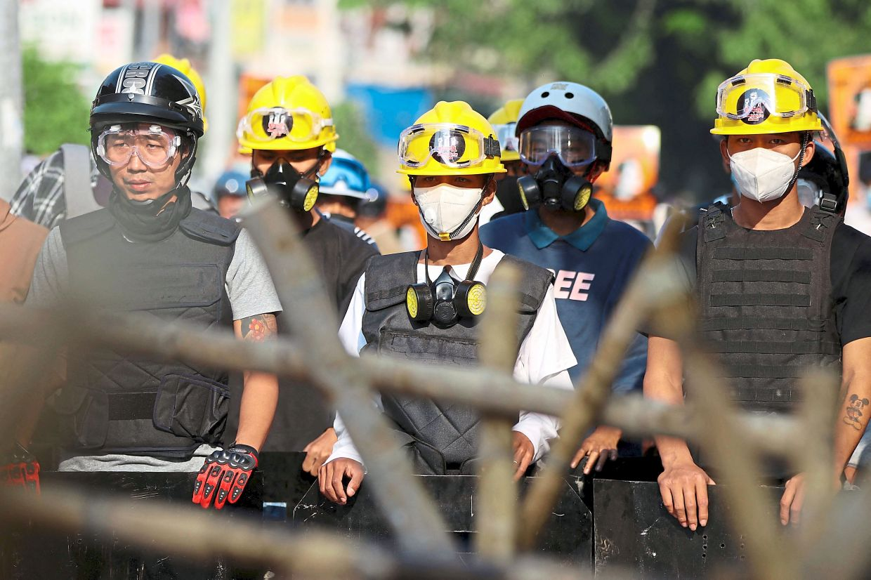 All geared up: Protesters standing behind a barricade as they face off with police during a demonstration in Naypyidaw. — AFP