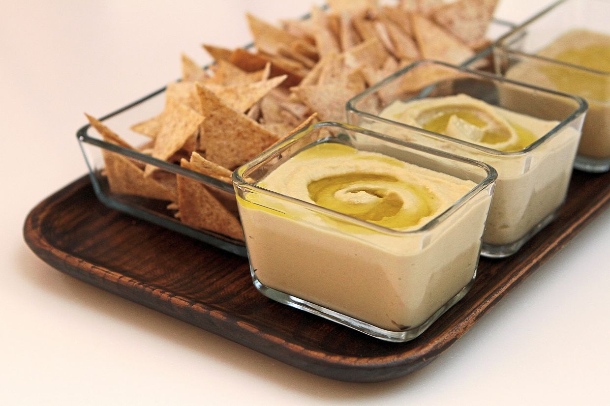 Served as an appetiser with toasted flatbread, the hummus, baba ghanoush and tahini dips are garnished with a drizzle of olive oil to keep them from drying out.