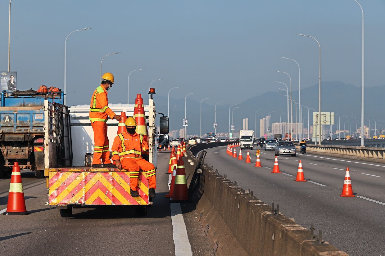 Workers cordoning off with cones the 635m stretch at KM3.2 where the power cable under the bridge caught fire.