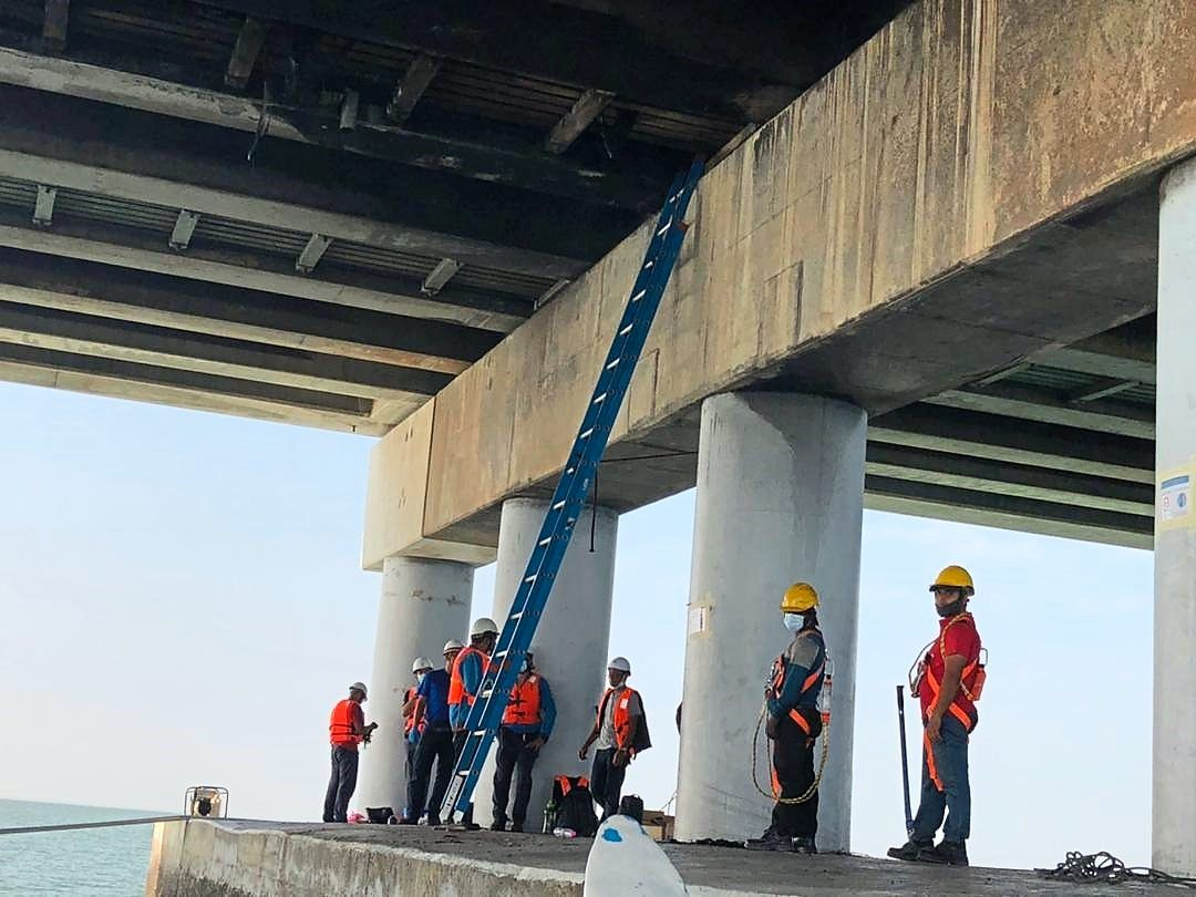 TNB technicians preparing to repair the burnt cable under Penang Bridge. — Courtesy phot