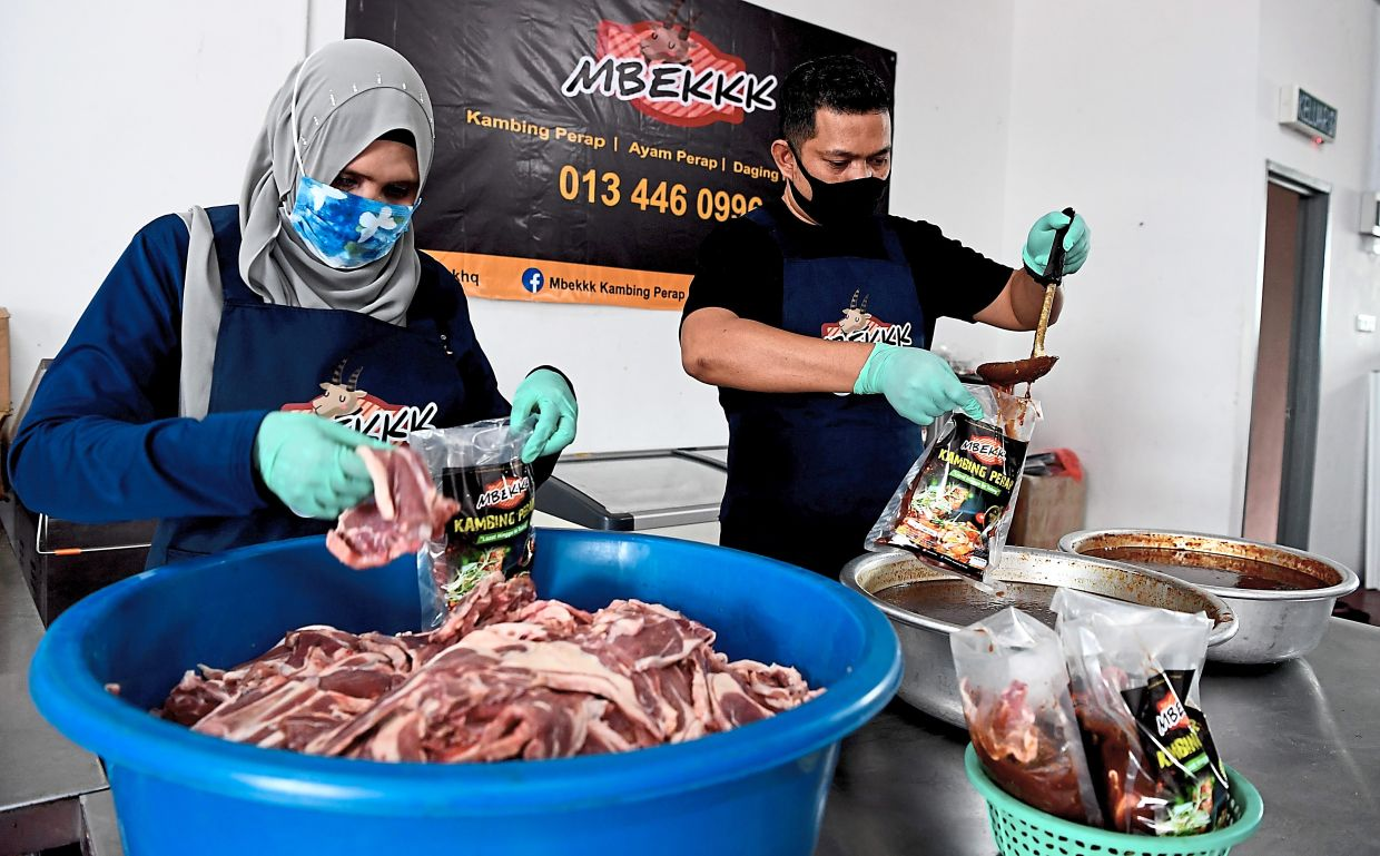 Roazian (left) and Rosnizam preparing the marinated lamb and chicken at their factory in Kepala Batas, Penang.