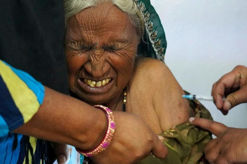 An elderly woman reacts as she is inoculated with the Covid-19 coronavirus vaccine at a government hospital on the outskirts of Ajmer on March 6, 2021. - AFP