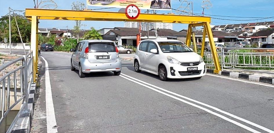 The Taman Dahlia Bridge in Butterworth with the height barrier intact (pic, below) and after the structure was knocked down by a lorry.