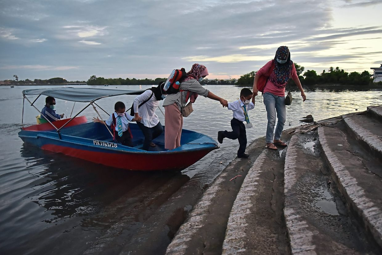Easy does it: Mothers helping their schoolchildren get off a boat at a jetty in Labuan.  — Bernama