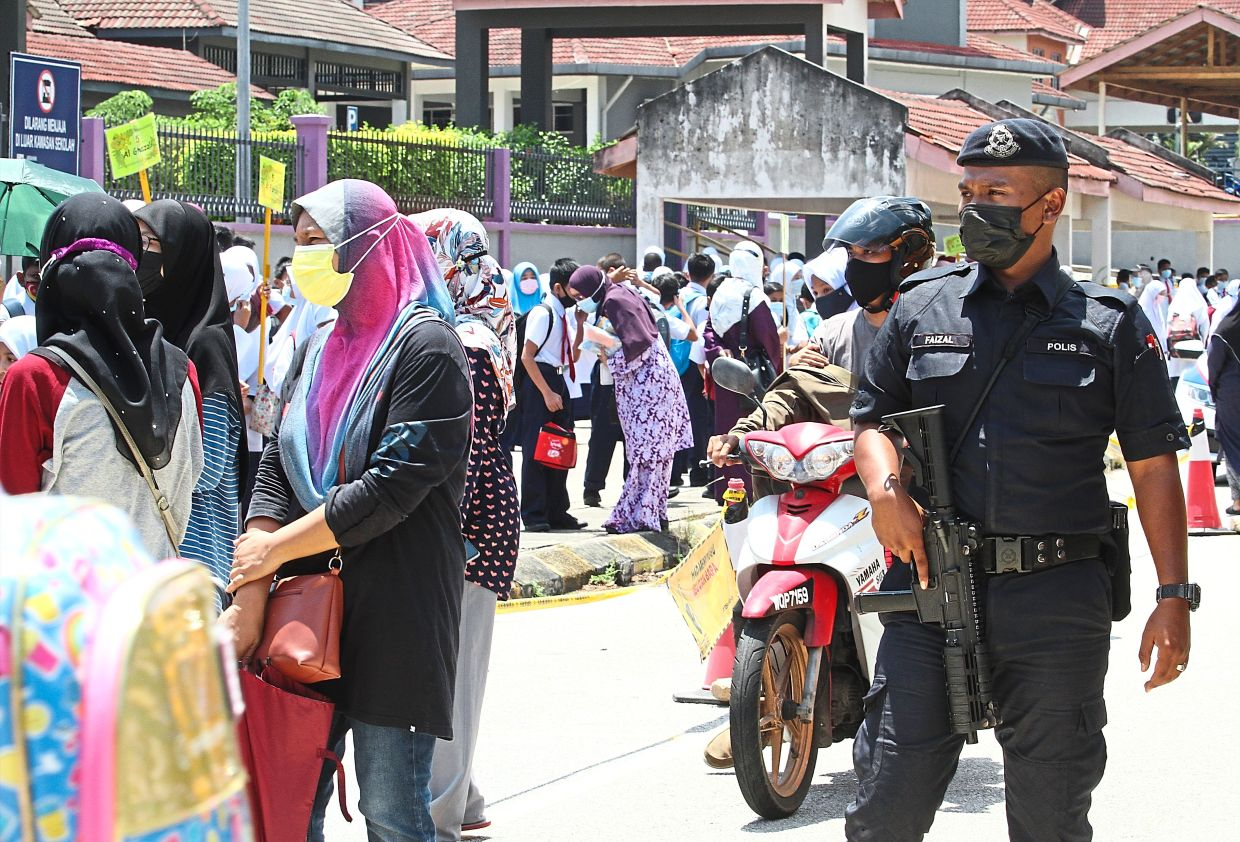Keeping an eye on things: A policeman standing guard as parents drop their children off at a school. — AZLINA ABDULLAH/The Star