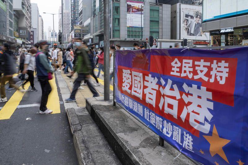 Pedestrians walk past a banner reading