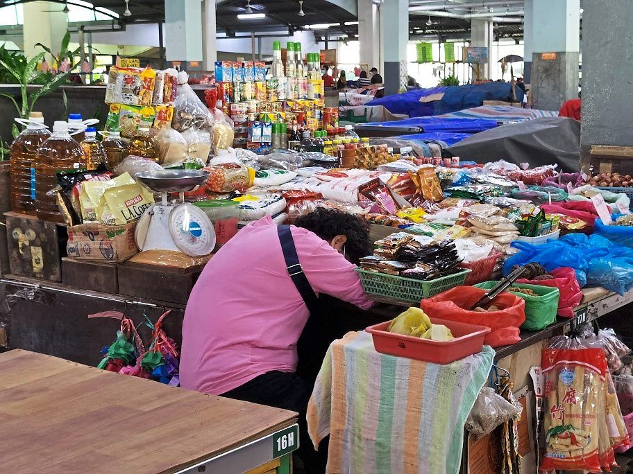 A hawker dozing off as there is almost no business at the market.
